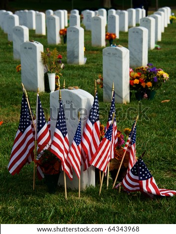 Tombstones at Arlington National Cemetery with flags and flowers