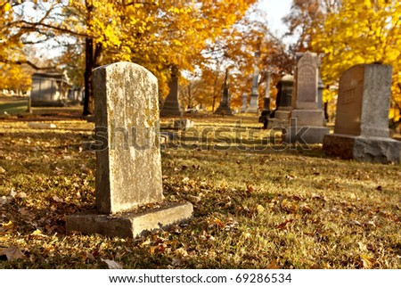 Tombstones in an old cemetery in the fall, selective focus