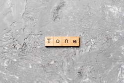 tone word written on wood block. tone text on cement table for your desing, concept.