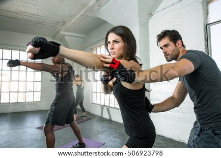 Toned fitness boxing Instructor assists female student punch cardio weight loss gym trainer