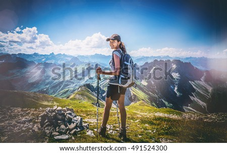 Toned image of an attractive young Indian woman backpacking in the Allgau Alps, Germany standing on an alpine plateau looking back with a smile, heavy vignette and flare effect