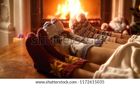 Toned image of family feeling cosy by the fireplace at house #1172615035