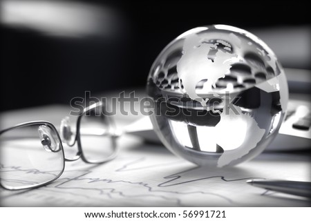 Toned image of glass globe with stock charts, calculator and spectacles - stock photo