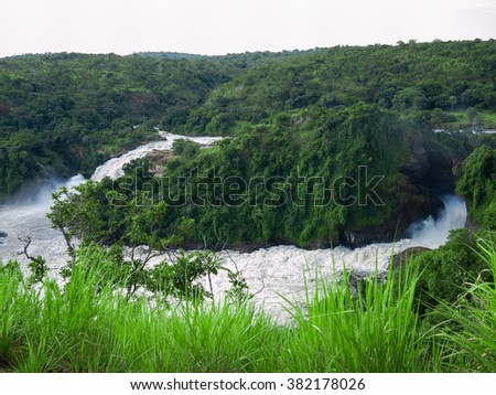 Toned image of majestic waterfall in the park Murchison Falls in Uganda against the background of the jungle and the sky