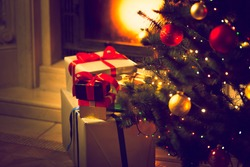 Toned photo of decorated Christmas tree and gift boxes against burning fireplace