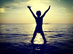 Toned photo of Happy Kid silhouette in the Sea