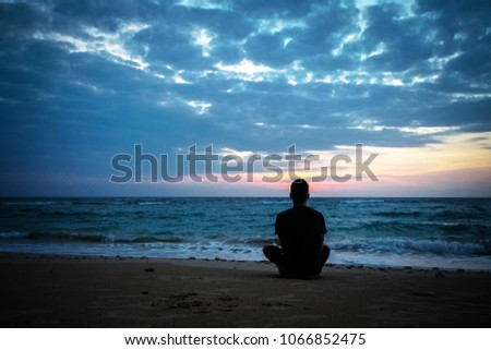 Toned Photo of Lonely Man sit at Sunset Background. lonely young guy sitting one in Lotus position on the beach ocean on background of cloudy sky. rest, relax, recreation leisure recreational activity #1066852475
