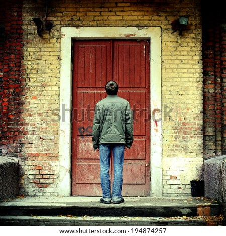 Toned photo of Man stand before Old House with closed Door