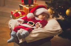 Toned photo of newborn baby boy dressed in Santa costume lying with Christmas gifts