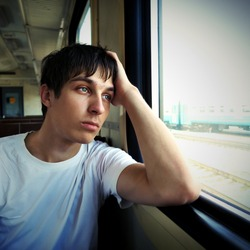 Toned Photo of Sad Young Man sit in the Train by the Window