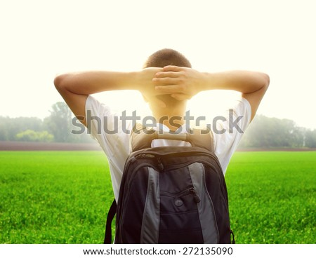 Toned Photo of teenager with knapsack in the summer field