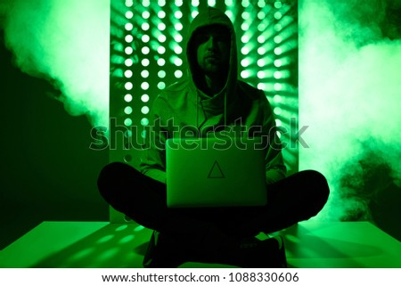 toned picture of hacker in hoodie with laptop and triangle sign on it
