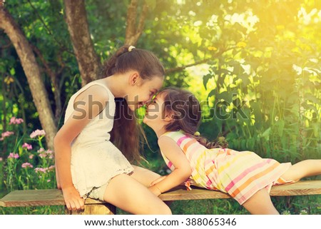 Toned portrait of two cute little girls smiling and playing at the garden #388065346