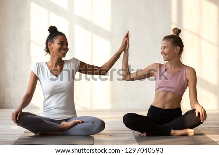 Toned smiling diverse girls sit on rubber mats give high five happy for good result practicing yoga, African American and Caucasian yogi join hands motivated for success, show unity and support
