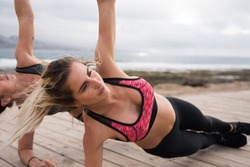 Toned women staying fit by the sea side with muscle strengthening excercises wearing beautiful fitness wear