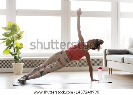 Toned young woman in sportswear lying on fitness mat at home doing side plank training alone, fit millennial girl perform workout in living room, improving body shape toning abs muscles