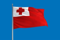 Tonga national flag waving in the wind on a deep blue sky. High quality fabric. International relations concept.