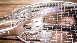 Tongs and is grates lay on the table that prepared and waiting for stove to fill in the table hole to grill the meat and BBQ