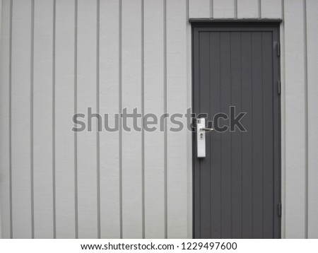 Tongue and groove wood paneling grey wall and door.