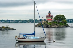 Too cloudy for sailing near Pomham Rock Lighthouse in Providence, Rhode Island. Sailboat is moored near lighthouse for protection.