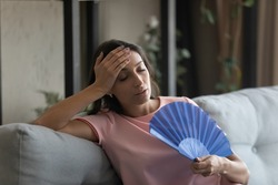 Too hot. Exhausted indian female suffer from heat in modern apartment use hand fan feel lack of air conditioning. Unhappy young mixed race female complaining on high temperature at home hard to breath