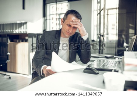 Too many complications. Businessman having too many complications while working on report in the office