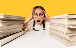 Too Much Homework. Shocked Overworked Asian Schoolgirl Cupping Head In Hands Sitting Between Two Books Stacks Over Yellow Studio Background.