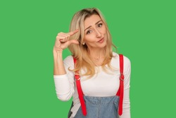 Too small! Portrait of dissatisfied adult woman with apologizing look showing a little bit gesture, inch or centimeter, disappointed with minimum size. indoor studio shot isolated on green background