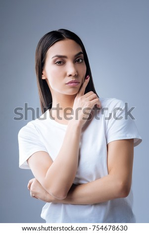 Too strict. Beautiful serious professional manager standing against the blue background with her finger up near her face while looking into the distance and expressive no positive emotions #754678630
