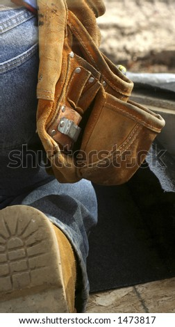 Tool belt in use by a roofer - stock photo