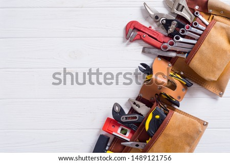 Tool belt with hand tools . Work background on wooden board #1489121756