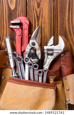 Tool belt with hand tools . Work background on wooden board