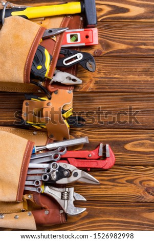 Tool belt with hand tools . Work background on wooden board #1526982998