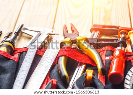Tool belt with tooling construction level protective gloves on wooden board.Carpenter tools – A carpenters bench with various tools #1566306613
