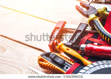 Tool belt with tooling construction level protective gloves on wooden board.Carpenter tools – A carpenters bench with various tools #1566306616