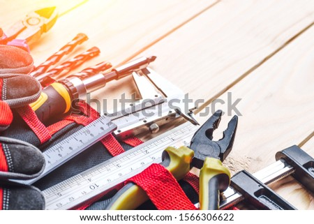 Tool belt with tooling construction level protective gloves on wooden board.Carpenter tools – A carpenters bench with various tools #1566306622