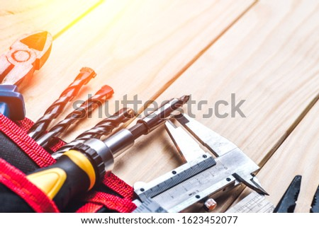 Tool belt with tooling construction level protective gloves on wooden board.Carpenter tools – A carpenters bench with various tools