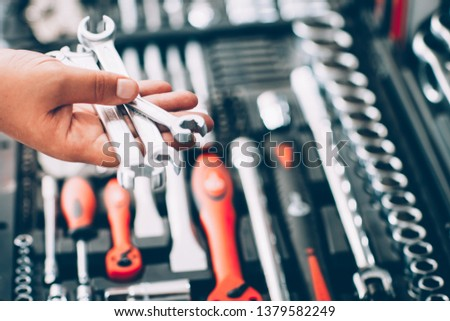 Tool hardware store. Closeup of male hand holding wrenches and spanners. Auto repair kit in toolbox. Repairman instruments set. #1379582249