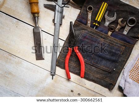 tool kit and jean bag on brown wood