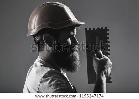 Tool, trowel, handyman, man builder. Mason tools, builder. Bearded man worker, beard, building helmet, hard hat. Builders in hard hat, helmet. Mason plastering. Plastering tools. Black and white.