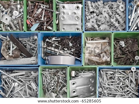 Toolbox full of metallic screws and consumable hardware