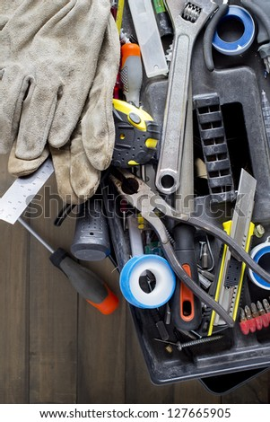 Toolbox with various tools on a wooden surface.