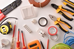 Tools and electrical material on a white table general view Horizontal composition. Top view.