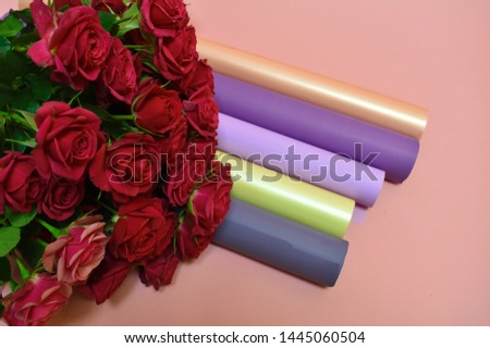 Tools and materials of the florist. Beautiful pleasant work. Concept of flower salon.  A packing material for flowers. Rose bushes on beautiful pink background.