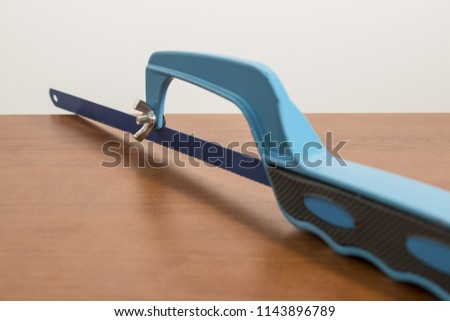 Tools, blue hacksaw on a wood table composition