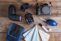 Tools for cleaning camera with dslr camera and lens, flash, pen brush with accessory kit bag. Different objects on wooden background. Top view.