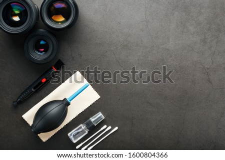 Tools for cleaning the camera with lenses on a dark textured background.
