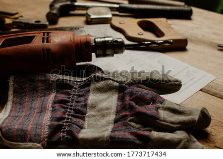 Tools for construction and carpentry: industrial gloves, drill, hammer and meter on wooden table. home repair concept.