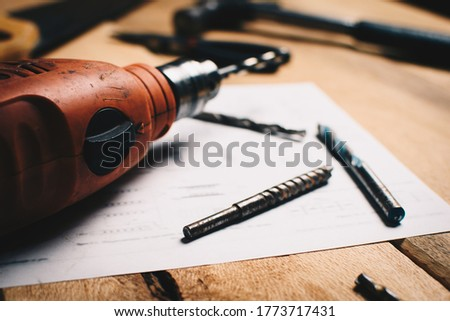Tools for construction and carpentry: steel drill bits on planes accompanied by tools in the background. DIY and designs concept.