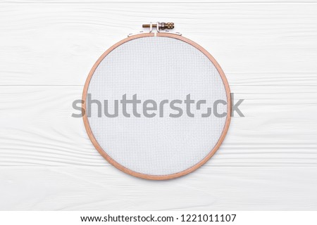 Tools for cross stitch. A hoop for embroidery and canvas on white wooden background. Mockup for hobby Stock photo ©